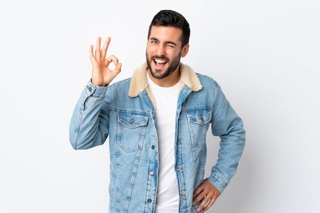 Młody przystojny mężczyzna z brodą odizolowywającą na biel ścianie pokazuje ok znaka z palcami