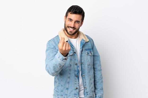 Młody przystojny mężczyzna z brodą odizolowywającą na biel ścianie robi pieniądze gestowi