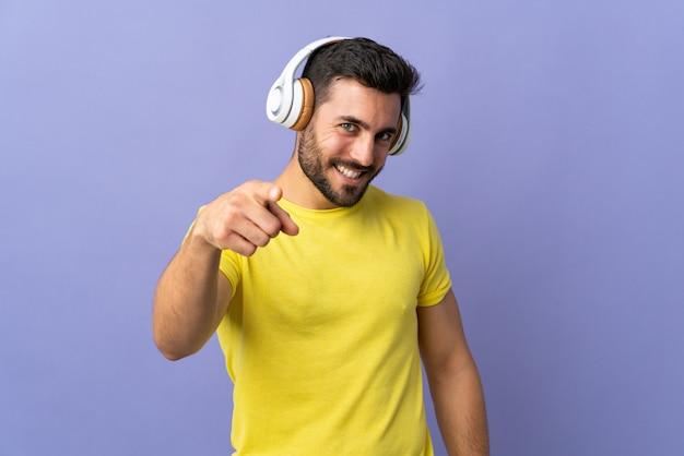 Młody przystojny mężczyzna z brodą odizolowywającą na purpurach izoluje słuchającą muzykę