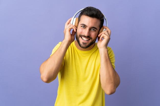 Młody przystojny mężczyzna z brodą odizolowywającą na purpurowej słuchającej muzyce