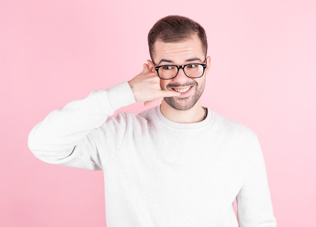 Młody przystojny mężczyzna z brodą robi gest telefonu ręką i palcami, jak rozmawia przez telefon.