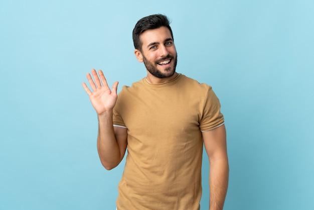Młody przystojny mężczyzna z brodą salutuje z ręką z szczęśliwym wyrażeniem