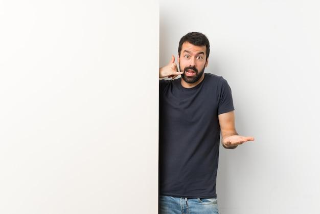 Młody przystojny mężczyzna z brodą trzyma duży pusty plakat robi telefonu gestowi i wątpi