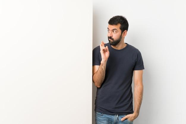Młody przystojny mężczyzna z brodą trzyma duży pusty plakat z palcami skrzyżowanymi i życząc jak najlepiej
