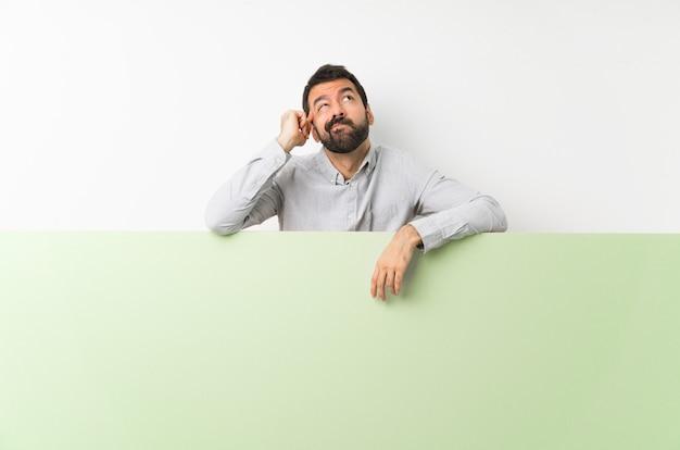 Młody przystojny mężczyzna z brodą trzyma duży zielony pusty plakat