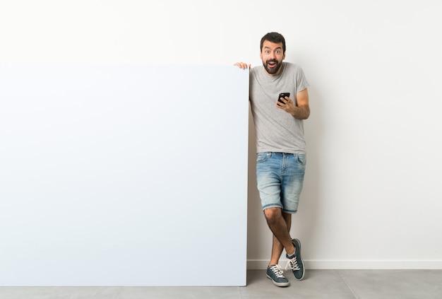 Młody przystojny mężczyzna z brodą, trzymając duży niebieski pusty plakat zaskoczony i wysyłanie wiadomości