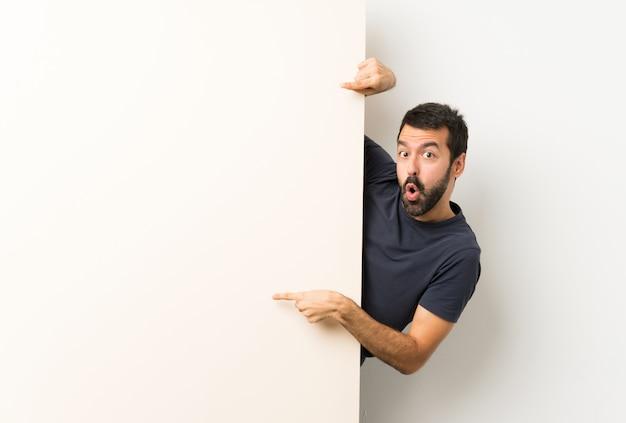 Młody przystojny mężczyzna z brodą, trzymając duży pusty plakat i wskazując go