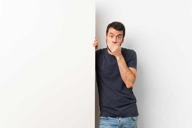 Młody przystojny mężczyzna z brodą, trzymając duży pusty plakat obejmujący usta rękami