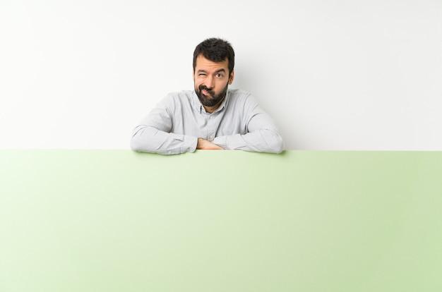 Młody przystojny mężczyzna z brodą, trzymając duży zielony pusty afisz uczucie zdenerwowany