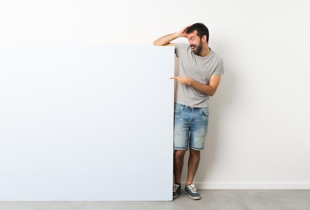 Młody przystojny mężczyzna z brodą, trzymając wielki niebieski pusty plakat zaskoczony i wskazując palcem na bok