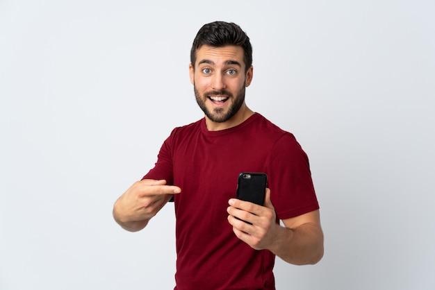 Młody przystojny mężczyzna z brodą używać telefon komórkowego odizolowywającego na biel ścianie i wskazujący je