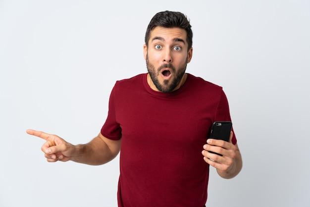 Młody przystojny mężczyzna z brodą używać telefon komórkowego odizolowywającego na bielu zaskakującej i wskazującej stronie