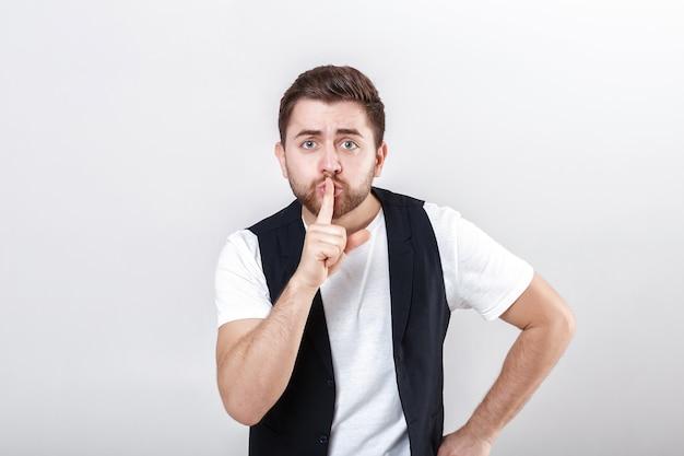 Młody przystojny mężczyzna z brodą w białej koszuli i czarnej kamizelce wykonujący gest ciszy
