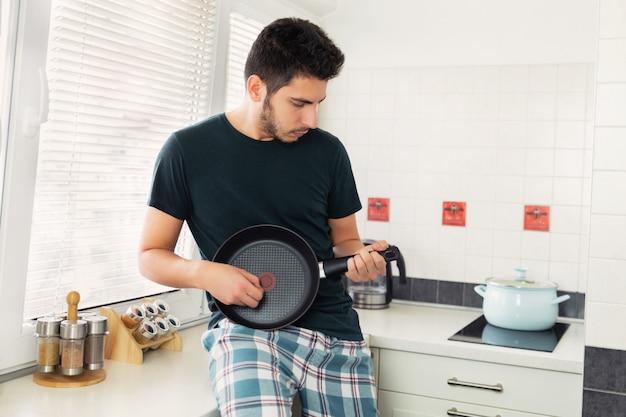 Młody przystojny mężczyzna z brodą w kuchni z ociekającym garnkiem jak gitara.