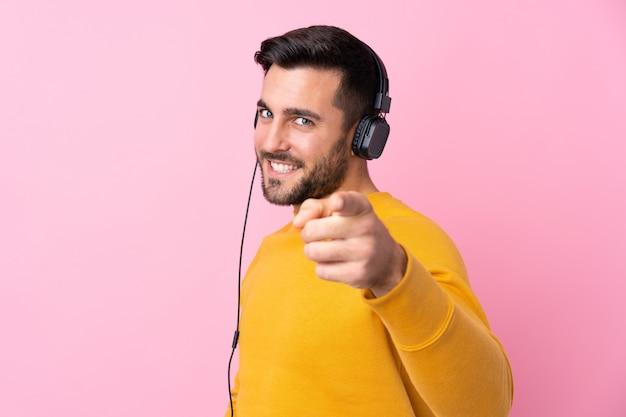 Młody przystojny mężczyzna z brody słuchającą muzyką nad odosobnioną menchii ścianą