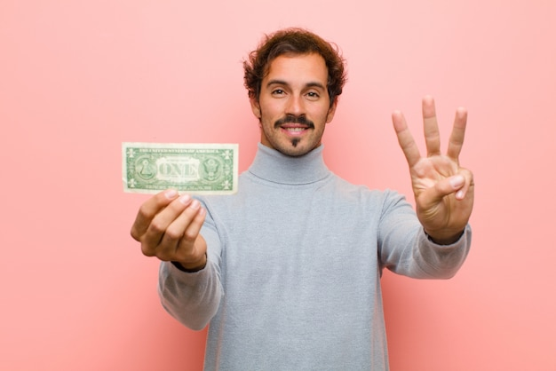 Młody przystojny mężczyzna z dolarowymi banknotami przeciw różowej płaskiej ścianie