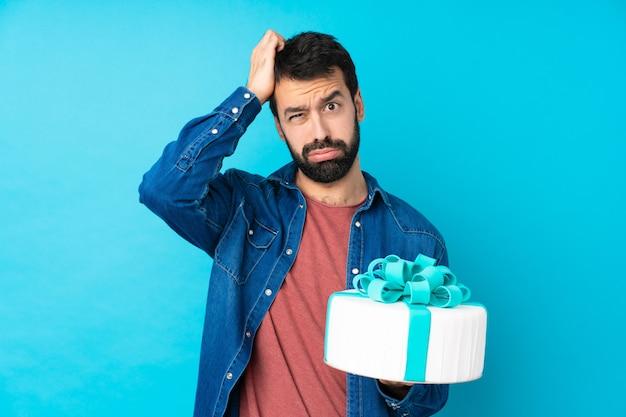 Młody przystojny mężczyzna z dużym ciastem na pojedyncze niebieskie ściany z wyrazem frustracji i braku zrozumienia