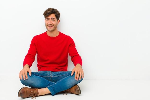 Młody przystojny mężczyzna z dużym, przyjaznym, beztroskim uśmiechem, wyglądający pozytywnie, zrelaksowany i szczęśliwy, relaksujący, siedząc na podłodze