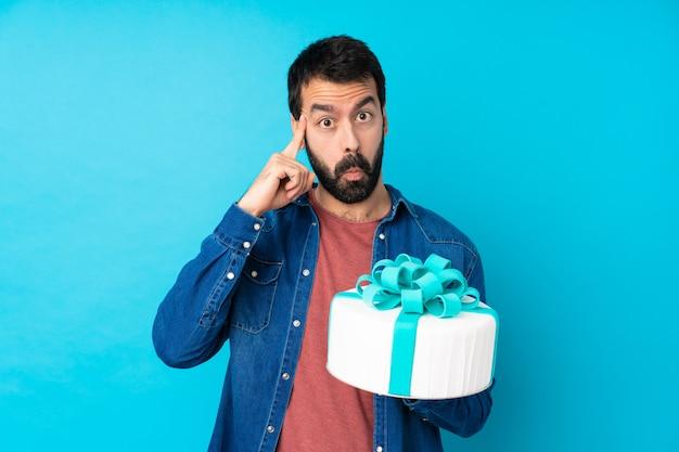 Młody przystojny mężczyzna z dużym tortem nad odosobnioną błękit ścianą myśleć pomysł