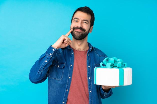 Młody przystojny mężczyzna z dużym tortem nad odosobnioną błękit ścianą ono uśmiecha się z szczęśliwym i przyjemnym wyrażeniem