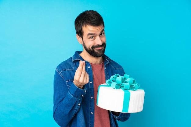 Młody przystojny mężczyzna z dużym tortem nad odosobnioną błękit ścianą robi pieniądze gestowi