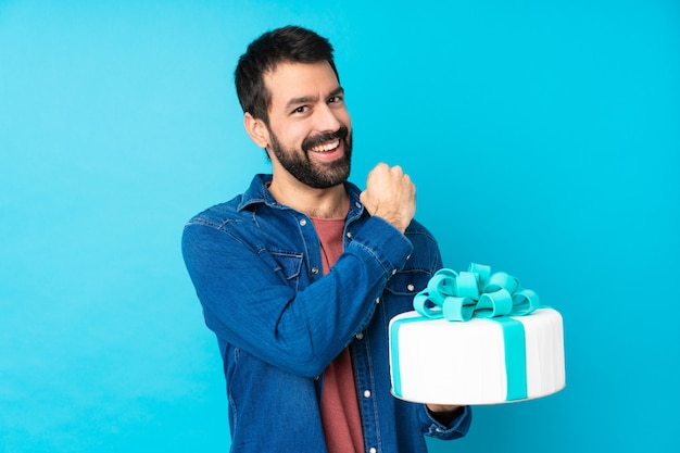 Młody przystojny mężczyzna z dużym tortem nad odosobnioną błękit ścianą świętuje zwycięstwo