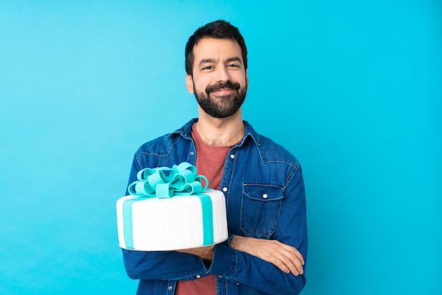 Młody przystojny mężczyzna z dużym tortem, trzymając ręce skrzyżowane w pozycji frontalnej
