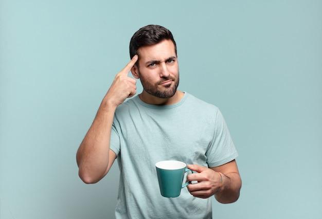 Młody przystojny mężczyzna z filiżanką kawy. koncepcja śniadanie