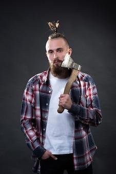 Młody przystojny mężczyzna z gęstą brodą i dużym wąsem w kraciastej koszuli goli brodę siekierą w studio na ciemnym tle