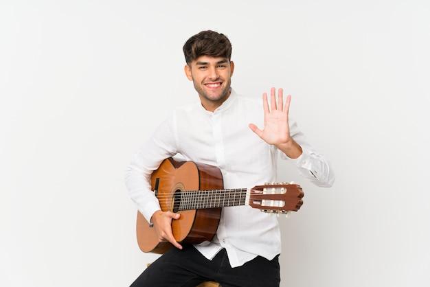 Młody przystojny mężczyzna z gitarą nad odosobnioną biel ścianą salutuje z ręką z szczęśliwym wyrażeniem