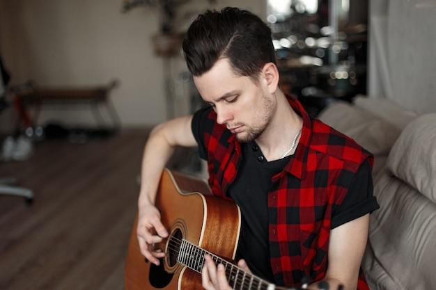 Młody przystojny mężczyzna z gitarą siedzi na kanapie
