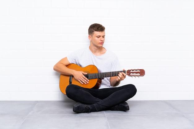 Młody przystojny mężczyzna z gitarą