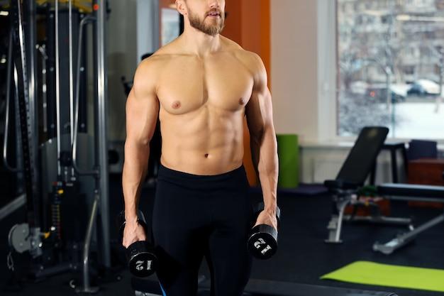Młody przystojny mężczyzna z hantlami, trening w siłowni