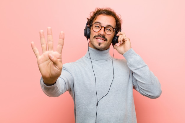 Młody przystojny mężczyzna z hełmofonami przeciw różowej płaskiej ścianie