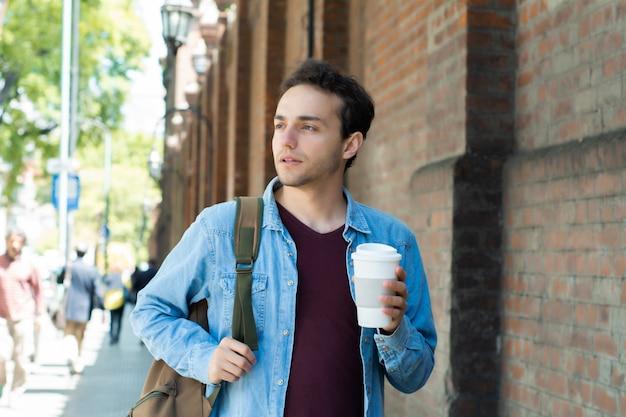 Młody przystojny mężczyzna z jednorazową kawą