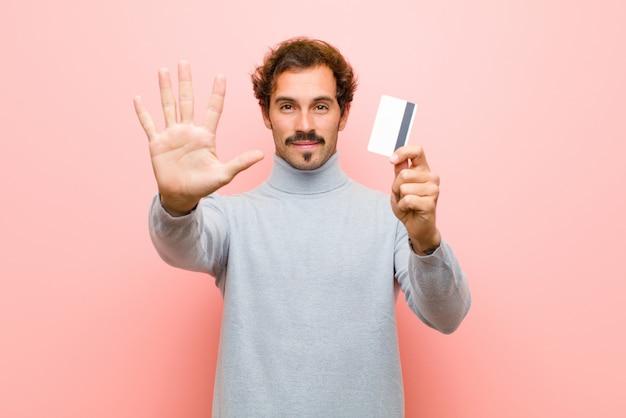 Młody przystojny mężczyzna z kartą kredytową przeciwko różowej płaskiej ścianie