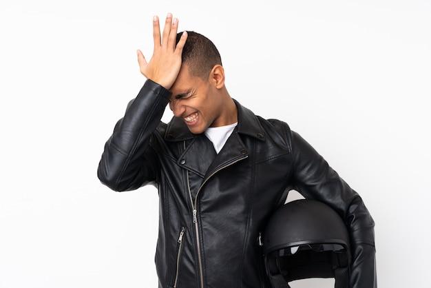 Młody przystojny mężczyzna z kaskiem motocykla na pojedyncze białe ściany, mając wątpliwości z dezorientacją wyrazem twarzy