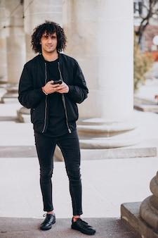 Młody przystojny mężczyzna z kręconymi włosami rozmawia przez telefon