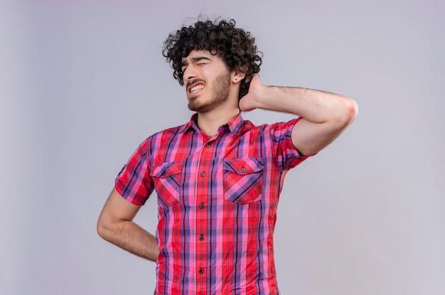 Młody przystojny mężczyzna z kręconymi włosami w koszuli w kratę, trzymający rękę na głowie i źle się czujący