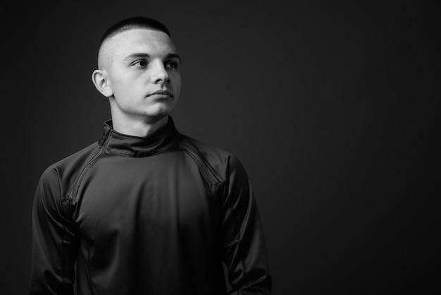 Młody przystojny mężczyzna z krótkimi włosami na sobie koszulę z wysokim kołnierzem na szarej ścianie. czarny i biały