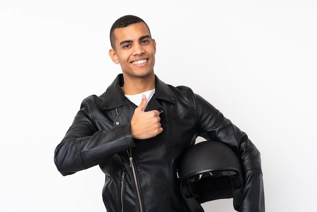 Młody przystojny mężczyzna z motocykla hełmem nad odosobnioną biel ścianą daje aprobata gestowi