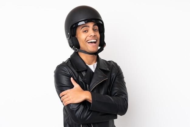 Młody przystojny mężczyzna z motocykla hełmem nad odosobnioną biel ścianą