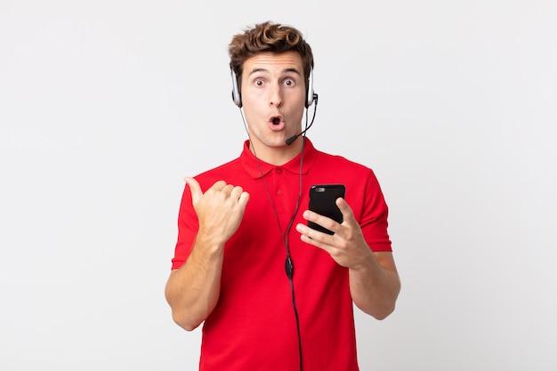Młody, przystojny mężczyzna z niedowierzaniem patrzący ze smartfonem i zestawem słuchawkowym
