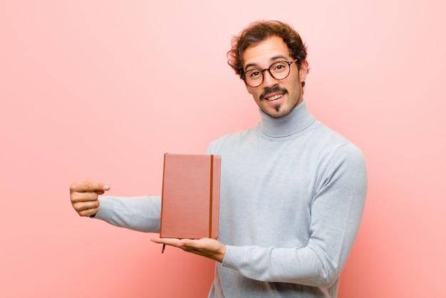 Młody przystojny mężczyzna z nutową książką przeciw różowej płaskiej ścianie