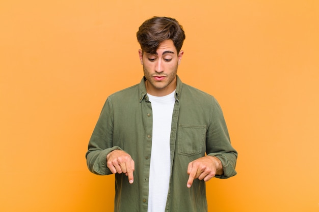 Młody przystojny mężczyzna z otwartymi ustami skierowanymi w dół obiema rękami, zszokowany, zaskoczony i zaskoczony pomarańczową ścianą