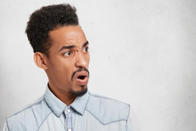 Młody przystojny mężczyzna z owalną podłużną twarzą, brodą i wąsami, wygląda na oburzonego i zniesmaczonego