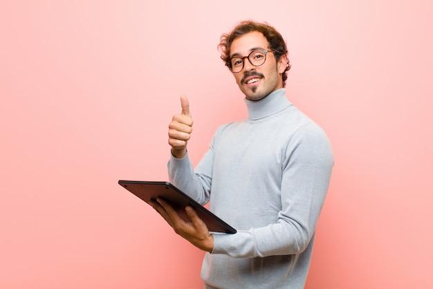 Młody przystojny mężczyzna z pastylki różową płaską ścianą