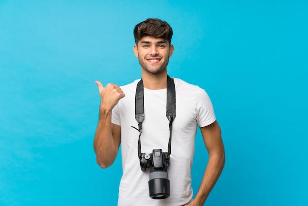 Młody przystojny mężczyzna z profesjonalnym aparatem i wskazując na bok