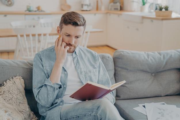 Młody przystojny mężczyzna z ręką na twarzy trzymający ołówek, czerwoną książeczkę na kolanie, wykonujący skupiony i poważny gest, mający za zadanie znalezienie nowych pomysłów, zastanowienie się, co zapisać