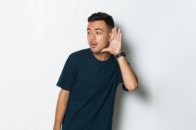 Młody przystojny mężczyzna z ręką na uchu słuchający przesłuchania plotek na białym tle